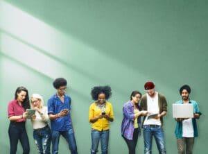 pessoas usando celulares com uma parede verde no fundo