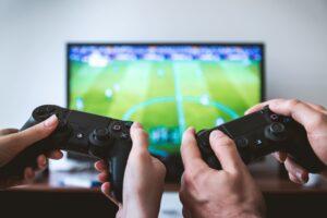 2 pessoas jogando um simulador de esporte de futebol