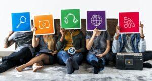pessoas segurando simbolos de aplicativos simbolizando a tecnologia criativa