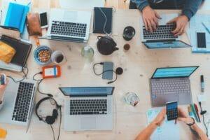mesa de trabalho com muitos notebooks utilizando o conceito de tecnologia criativa