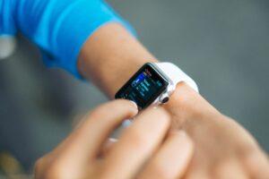 braço da mulher com uma smartfit nos braços